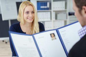 Frau im Bewerbungsgespräch mit Bewerbungsmappe